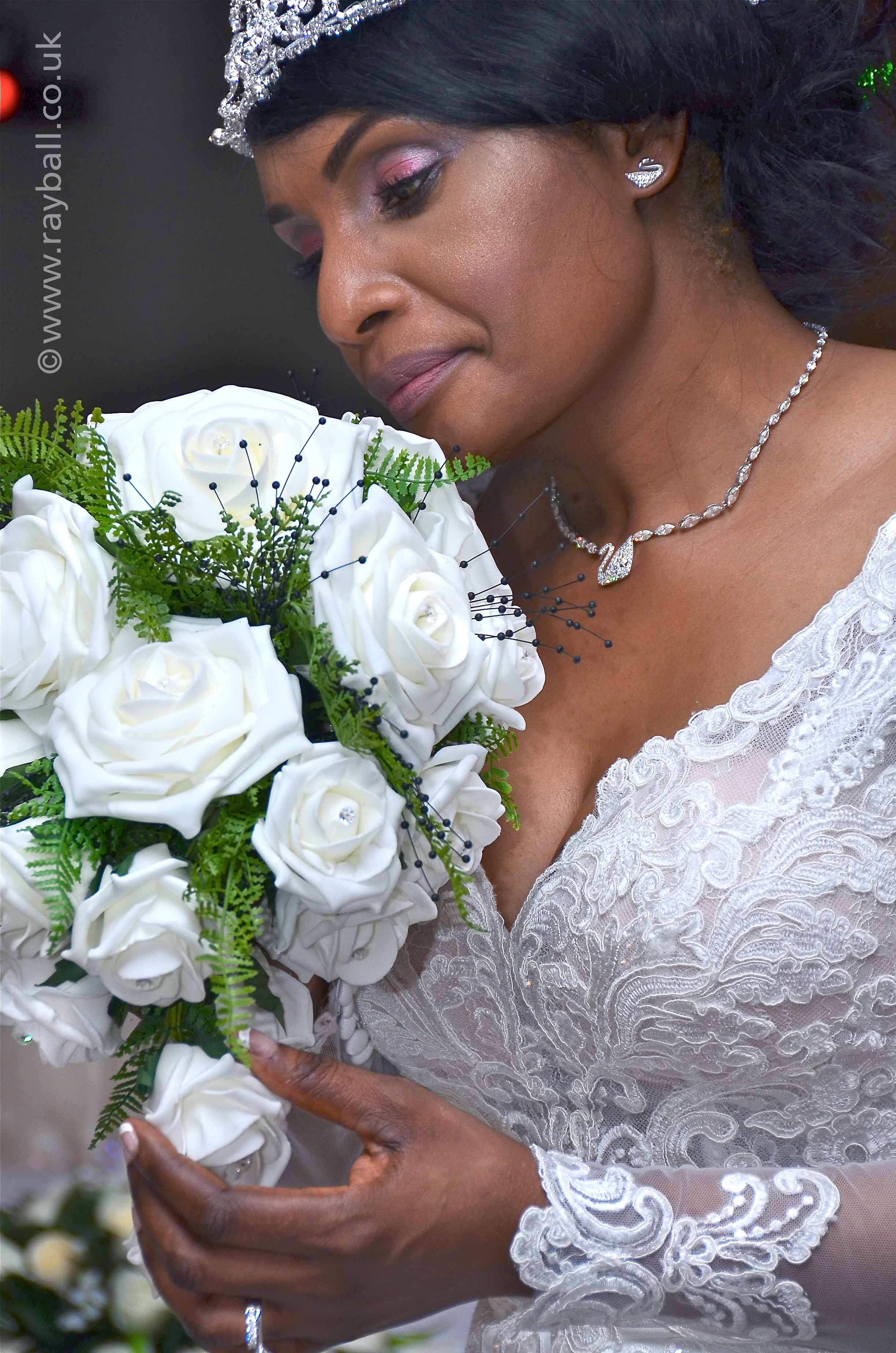 Pensive Epsom bride admiring her bouquet of white roses during a quiet moment at her eventful church wedding at Sanderstead, South Croydon. Epsom Photography Surrey..
