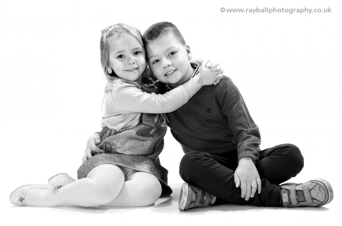 Handsome brother and sister from Ashstead posing for their portrait together at Epsom Photography Studio Surrey.