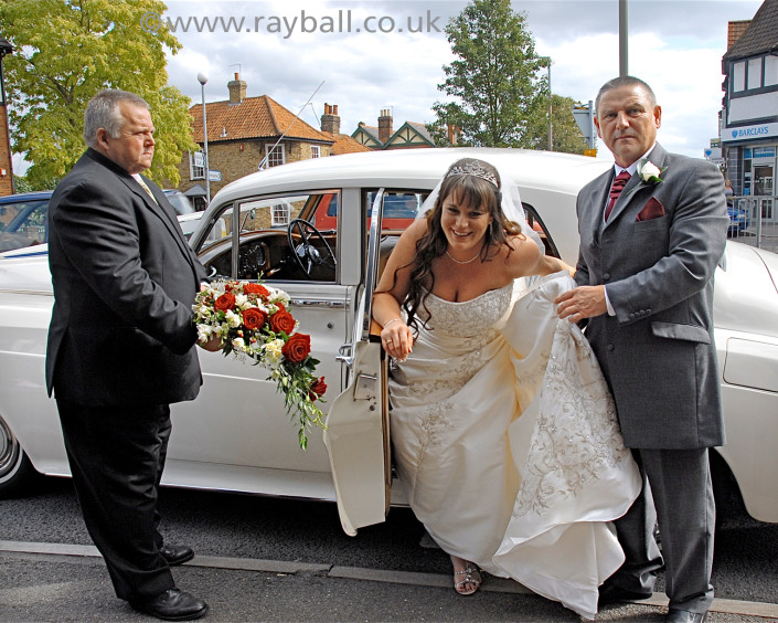 Bride struggling with dress exiting wedding car in Wandsworth by Epsom Photography