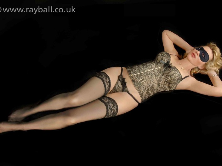 Tadworth model in mask and basque on black ground.