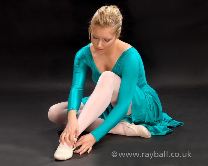 Tolworth dancer in blue dres adjusting her ballet shoe.