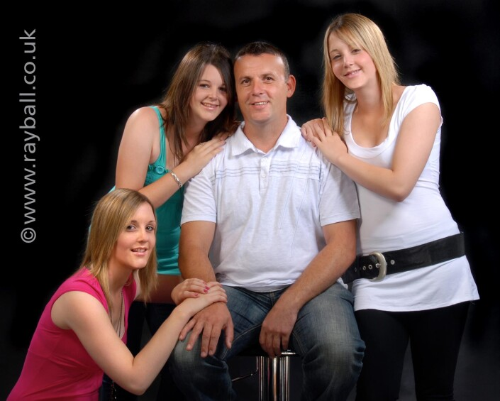 Studio portrait of three daughters and their dad from Sutton.