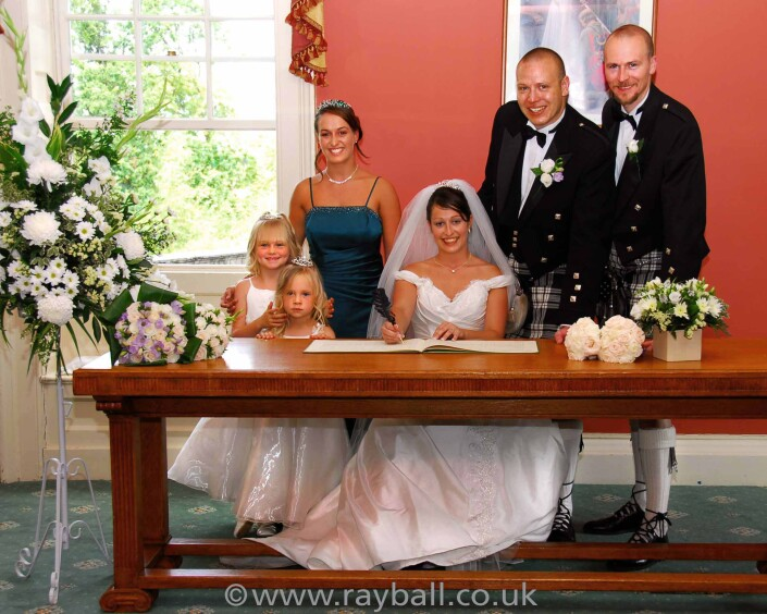 Sutton bride signs the register with her entourage.